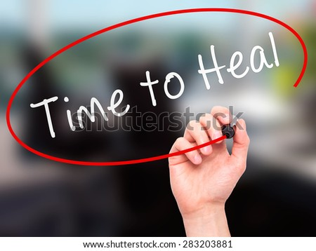 Man Hand writing Time to Heal with marker on transparent wipe board. Isolated on office. Business, internet, technology concept. Stock Photo - stock photo