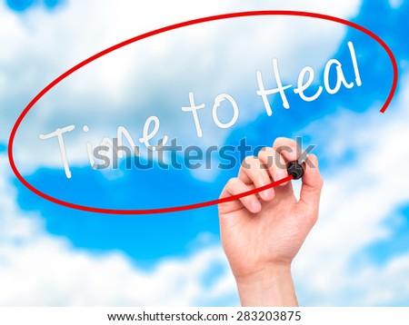 Man Hand writing Time to Heal with marker on transparent wipe board. Isolated on sky. Business, internet, technology concept. Stock Photo - stock photo