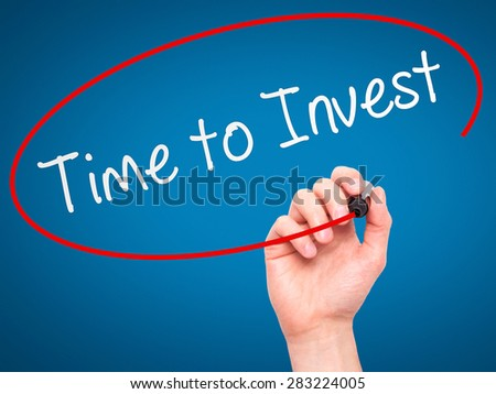 Man Hand writing Time to Invest with marker on transparent wipe board. Isolated on blue. Business, internet, technology concept. Stock Photo - stock photo