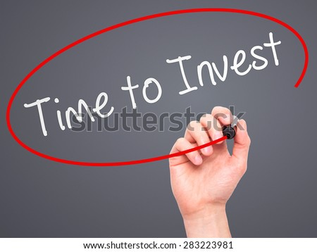 Man Hand writing Time to Invest with marker on transparent wipe board. Isolated on grey. Business, internet, technology concept. Stock Photo - stock photo