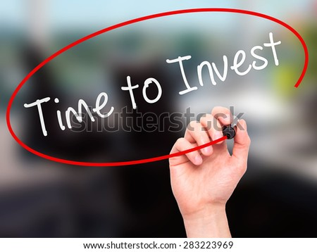 Man Hand writing Time to Invest with marker on transparent wipe board. Isolated on office. Business, internet, technology concept. Stock Photo - stock photo