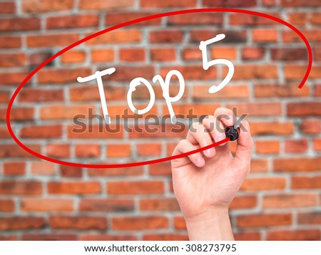 Man Hand writing Top 5 with black marker on visual screen. Isolated on bricks. Business, technology, internet concept. Stock Photo - stock photo