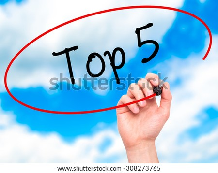 Man Hand writing Top 5 with black marker on visual screen. Isolated on sky. Business, technology, internet concept. Stock Photo - stock photo
