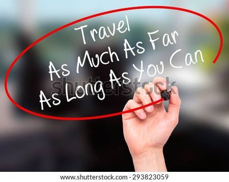 Man Hand writing Travel As Much As Far As Long As You Can  with black marker on visual screen. Isolated on office. Business, technology, internet concept. Stock Photo
