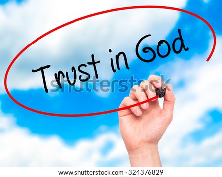 Man Hand writing Trust in God with black marker on visual screen. Isolated on sky. Business, technology, internet concept. Stock Photo - stock photo