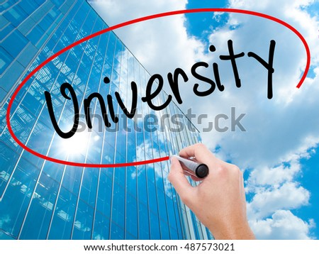 Man Hand writing University with black marker on visual screen. Business, technology, internet concept. Modern business skyscrapers background. Stock Photo