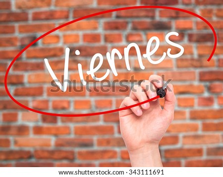 Man Hand writing Viernes (Friday in Spanish) with black marker on visual screen. Isolated on bricks. Business, technology, internet concept. Stock Photo - stock photo