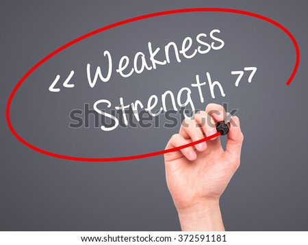Man Hand writing Weakness - Strength with black marker on visual screen. Isolated on background. Business, technology, internet concept. Stock Photo