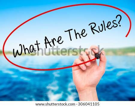 Man Hand writing What Are The Rules? with black marker on visual screen. Isolated on nature. Business, technology, internet concept. Stock Photo - stock photo