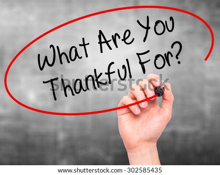 Man Hand writing What Are You Thankful For? with black marker on visual screen. Isolated on grey. Business, technology, internet concept.  - stock photo