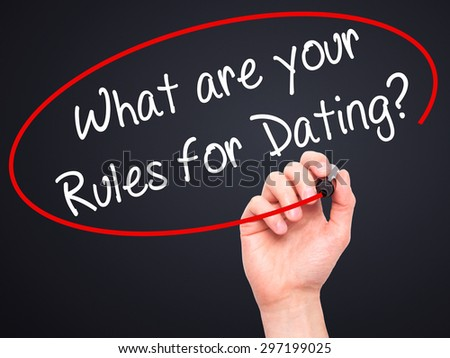 Man Hand writing What are your Rules for Dating?  with black marker on visual screen. Isolated on black. Business, technology, internet concept. Stock Photo