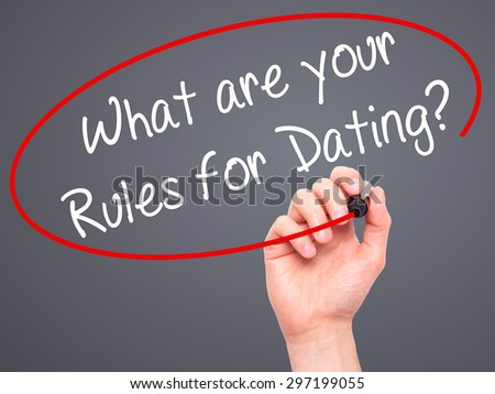 Man Hand writing What are your Rules for Dating?  with black marker on visual screen. Isolated on grey. Business, technology, internet concept. Stock Photo