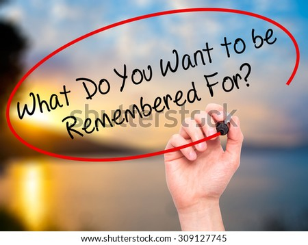 Man Hand writing What Do You Want to be Remembered For? with black marker on visual screen. Isolated on nature. Business, technology, internet concept. Stock Photo