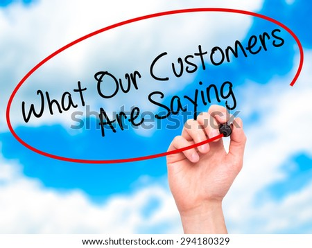 Man Hand writing What Our Customers Are Saying with black marker on visual screen. Isolated on sky. Business, technology, internet concept. Stock Photo - stock photo