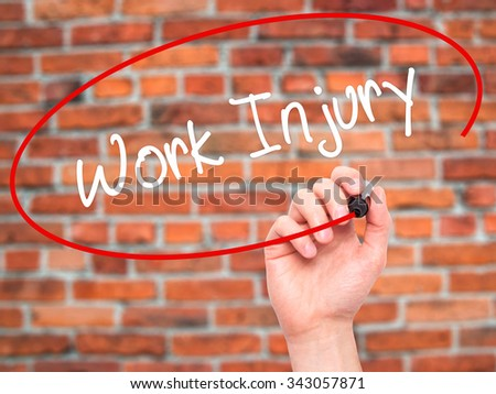 Man Hand writing Work Injury with black marker on visual screen. Isolated on bricks. Business, technology, internet concept. Stock Photo - stock photo