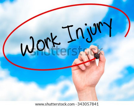 Man Hand writing Work Injury with black marker on visual screen. Isolated on sky. Business, technology, internet concept. Stock Photo - stock photo