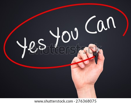 Man Hand writing Yes You Can with marker on transparent wipe board. Isolated on black. Business, internet, technology concept.  Stock Photo - stock photo