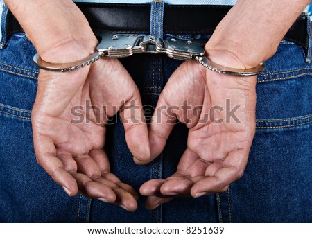 Man handcuffed hands at the back - stock photo