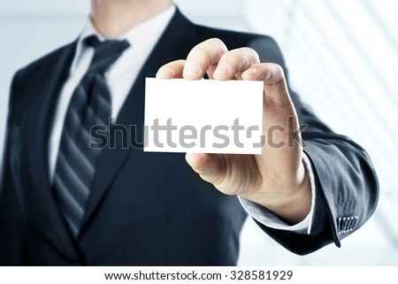 man handing a blank business card over blue background - stock photo