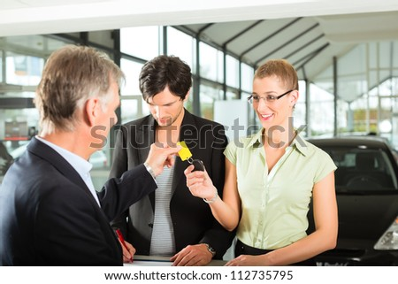 Man handing keys to new car to woman, her man signing the sales or rental contract - stock photo