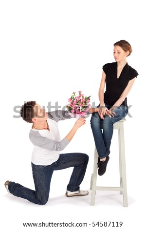 Man handing over bouquet of flowers to a beautiful young woman on Valentine Day isolated on white background - stock photo