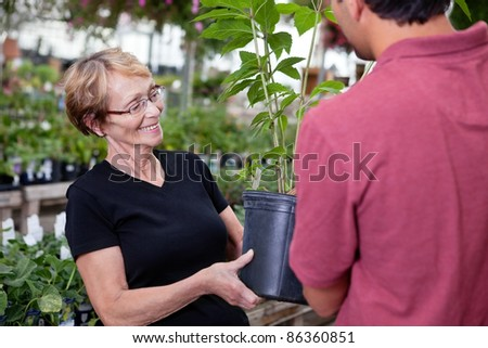 Man handing over potted plant to female customer