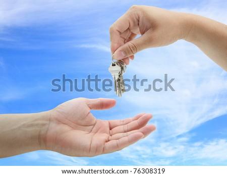 man handing over the set of keys house against blue sky - stock photo
