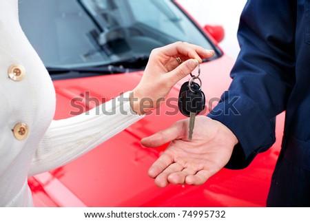 Man handing woman automobile keys. New Car - stock photo