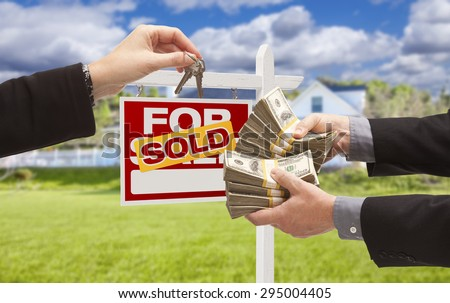 Man Handing Woman Thousands of Dollars For Keys in Front of House and Sold For Sale Real Estate Sign. - stock photo