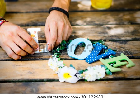 Man hands are doing love sign with colorful letters on the wooden table  - stock photo