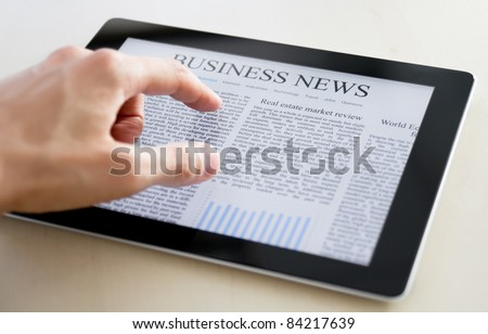 Man hands are pointing on touch screen device with business news. - stock photo