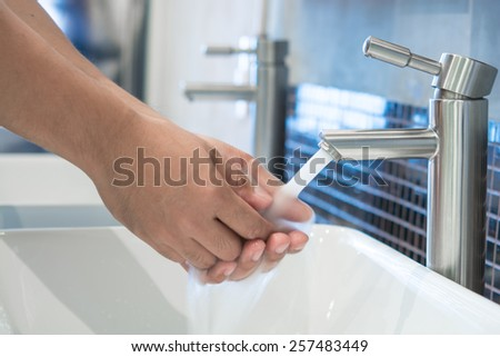 Man hands being washed under stream of pure water from tap - stock photo