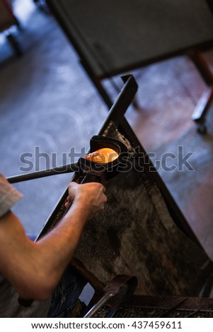 Man Hands Closeup Shaping a Blown Glass Piece with a Wooden Block - stock photo