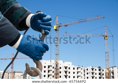 man hands closeup with crane hook at building background - stock photo