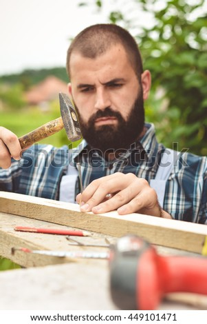 Man hands drive nail with a hammer in wooden
