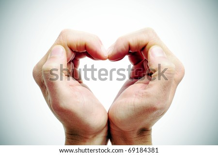 man hands forming a heart on a vignetted background - stock photo