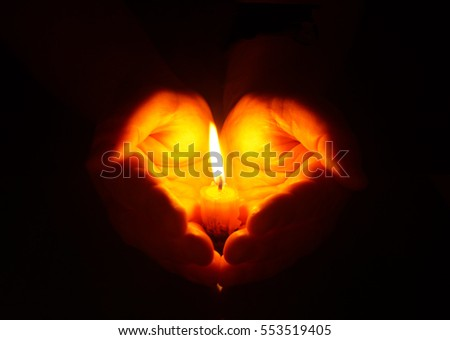 Man hands holding a burning candle in dark