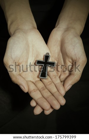 Man hands holding a cross on dark background
