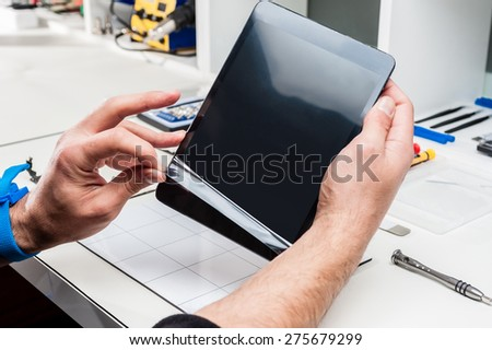 Man hands holding a tablet device. - stock photo