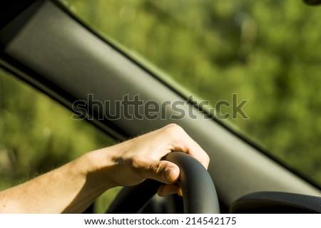 man hands holding black wheel - stock photo