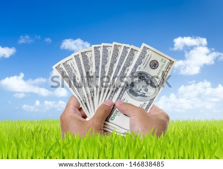 Man hands holding hundred dollar bills on green field with blue sky background - stock photo