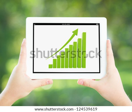 Man hands holding tablet PC against spring green background - stock photo