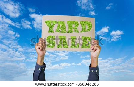 Man hands holding yard sale poster on blue sky background - stock photo