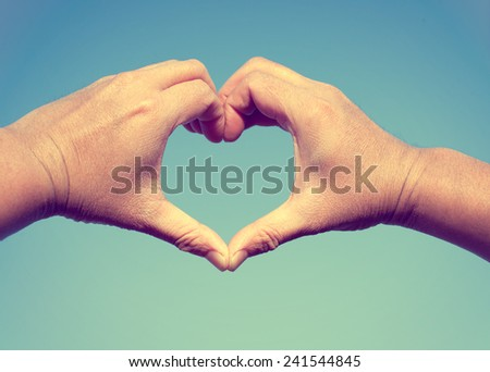 Man Hands in Heart Shape form love on Sky Background, love and valentine concept  (vintage color tone) - stock photo