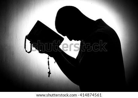 Man hands in prayer. Back light black and white. - stock photo