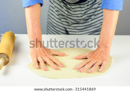 Man hands making dough for homemade dumplings with meat