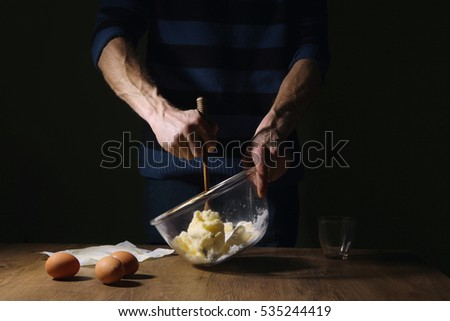 Man hands mixing sugar and butter  in bowl. Step of making cooking cake, preparing dough. Ingredients: butter, sugar, eggs.