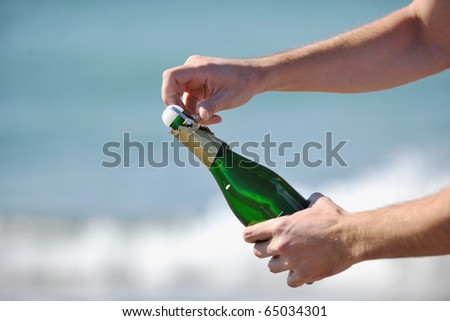 man hands open bottle of champagne alcohol and wine drink outdoor on party celebration event - stock photo