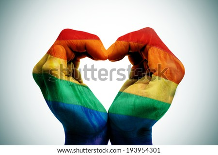 man hands patterned as the rainbow flag forming a heart, symbolizing gay love - stock photo