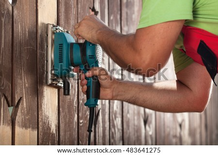 Man hands polishing old fence with power tool - a vibrating sander, closeup, slight motion blur